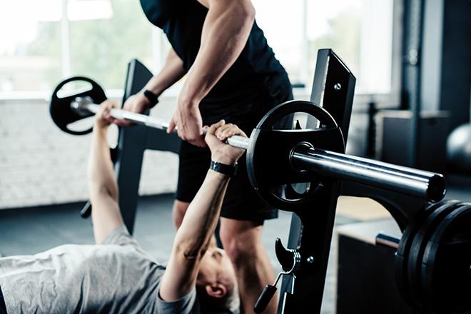 Sportcoach erteilt Hilfe beim Training mit Gewichten