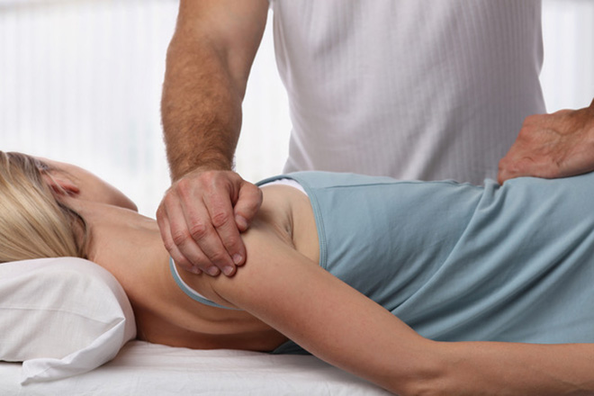 Oellerich Physiotherapie: Therapeut behandelt die Schulter einer Patientin